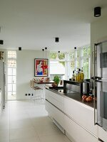 Open-plan kitchen with modern counter and dining area flanked by French doors in background