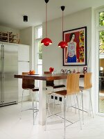 Counter with stainless steel base, bar stools with wooden shell seats, red pendant lamps and French windows to one side