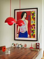 Red pendant lamp above walnut table below framed picture on wall