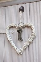 Heart-shaped wreath of white-painted straw and bunch of vintage keys on hook