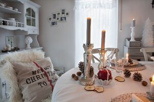 Lit candles in silver candlesticks and decorations on white tablecloth in vintage-style dining room