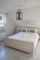 Double bed with white-painted wooden frame in rustic bedroom with romantic motto on wall