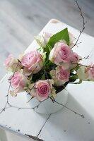 Vase of roses on white chair