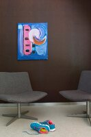 Blue artwork on dark brown wall and elegant lounge chairs
