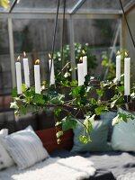 Kerzenleuchter mit weissen, brennenden Kerzen und Blätterzweigen