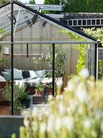 View into cosily furnished greenhouse with scatter cushions on corner sofa