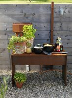 Potted herbs and bowls on rustic metal side table against wooden fence on gravel floor outdiirs