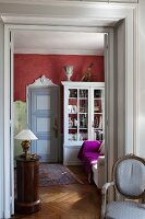 Antique, Rococo-style chair next to open double doors and view of white-painted display cabinet