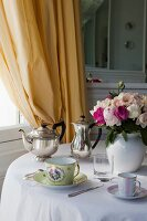 Cups, vase of flowers and silver teapot and coffee pot on round table