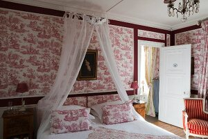 Double bed with canopy against red and white toile de jouy wallpaper