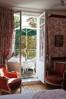 Antique armchairs flanking open French windows leading to seating area on balcony