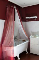 Free-standing, clawfoot bathtub under red and white fabric canopy