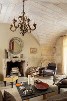 Vintage chandelier hanging from stone vault in rustic interior with open fireplace