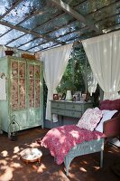 Antique furniture, quilt on chair, framed pictures on top of cabinet and shabby-chic cupboard in vintage-style conservatory