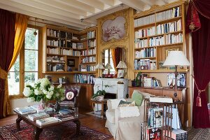 Bookcases, antique furniture and heavy curtains in vintage-style living room