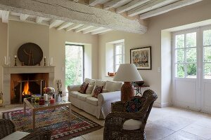 Wicker armchairs, sofa and coffee table in front of fireplace in renovated country house with whitewashed wood-beamed ceiling