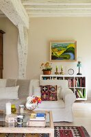 Coffee table, sofa with white loose cover and painting on wall above low shelving unit in interior with whitewashed wooden beams