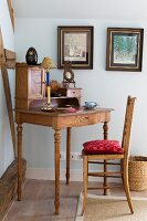 Simple wooden chair at antique bureau with turned legs in corner of room