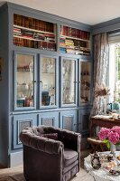 Country-house-style, floor-to-ceiling, fitted cabinets with glass doors and open-fronted shelves painted grey and blue