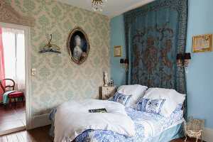 Elegant, traditional bedroom with brocade wallpaper, framed painting on woman and wall-hanging in French ambiance
