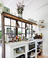 Weisse Küchenzeile vor Raumteiler mit Sprossenverglasung in schlichtem Holzhaus
