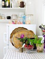 Ausschnitt einer Küchenzeile mit gefliester Arbeitsfläche, vor Kühlschrank mit Aufbewahrungsgläsern