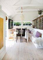 Dunkle Holzstühle vor Tisch und gemauerte Sitzbank weiss gestrichen in schlichtem Sommerhaus