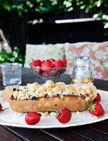 Selbstgebackener Beerenkuchen mit Streuseln und frische Erdbeeren auf Schale, im Freien