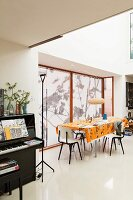 Open-plan interior; dining area with orange tablecloth, roller blinds on windows and black upright piano