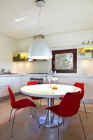 White round table and red designer chairs in white fitted kitchen with yellow lighting in wall units