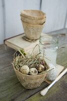 Easter nest of birds' eggs and hay in papier mâché pot hand-crafted from pages of vintage books on rustic wooden surface