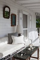 Finds on table with woven textile top and delicate bamboo bench on white wooden veranda