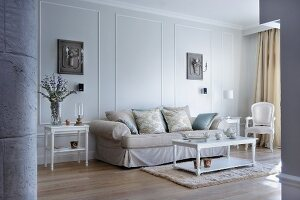 Elegant sofa and white, faux antique furniture against pale grey wall with stucco panels and sconce lamps on back plates