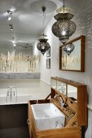 Oriental pendant lamps above custom-made washstand with lid; mirrored wall and pattern of grasses above bathtub in background