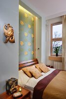 Niche with floral pattern and indirect lighting behind French bed; wooden sculpture on wall