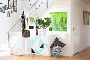 House plant on chest of drawers with graphic pattern and bags hung from coat rack next to staircase in modern foyer