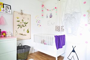 White cot below garland and vintage botanical illustration on wall of nursery