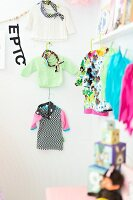 Children's clothing hung on wall and from line
