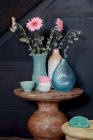 Pink gerbera daisies in various vases and pastel bowls on round stone table