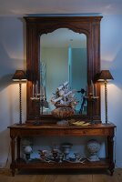 Table lamps on antique console table and wood-framed mirror