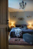 View through open door of double bed and suitcase in bedroom