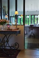 Antique, ornate metal serving trolley against partition with interior window and view into kitchen