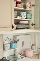 Stacked crockery with pastel floral patterns in wall-mounted cupboard above vintage-style enamel pots on kitchen worksurface