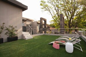 Artificial lawn, sun loungers and drinks on side table on roof terrace