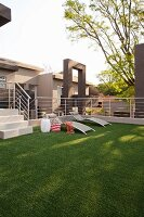 Artificial lawn, sun loungers and stainless steel balustrade on roof terrace
