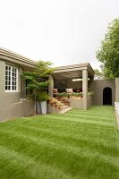 Large area of artificial lawn outside cubic house with steps leading to veranda