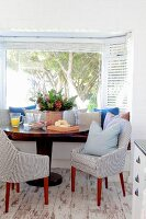 Dining area with bench and two striped easy chairs on old wooden floor in window niche