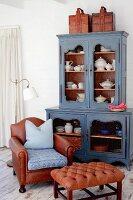 Vintage crockery in blue vintage dresser, brown leather armchair and Chesterfield footstool