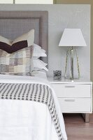 Patterned blanket on bed and table lamp on white bedside cabinet