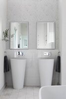 Twin designer pedestal sinks below mirrors on wall with delicate graphic pattern of leaves